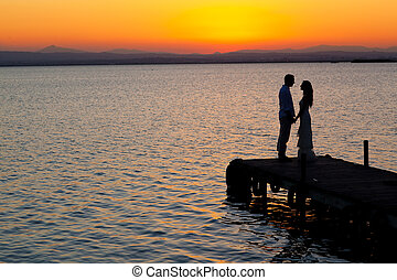 couple sunset profile back light in orange sea full length