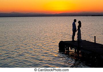 couple sunset profile back light in orange sea full length