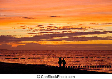 couple talking a walk at the beach at sunset
