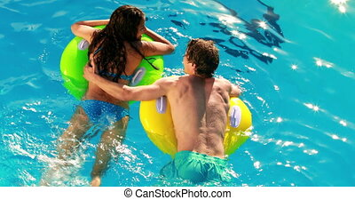 Couple swimming on inflatable rings