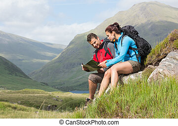 Couple taking a break after hiking uphill and reading map in...