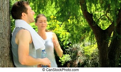 Man leaning against a tree giving his girfriend a drink and a towel after jogging