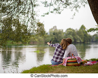 Couple taking a selfie by mobile phone while enjoying picnic time