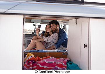 Couple taking a selfie in camper van at beach