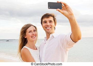 Couple taking a selfie on the beach at sunset