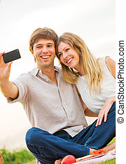 """Couple taking photo of themselves with smartphone on romantic picnic date, taking a """"selfie"""""""