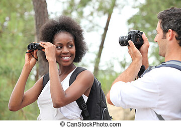 Couple taking photographs in forest