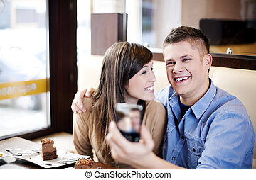 Couple taking picture in cafe
