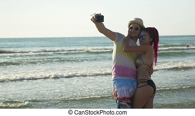 Couple taking selfie and having fun on the shore of a sandy beach