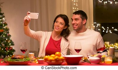 couple taking selfie at home christmas dinner - holidays,...