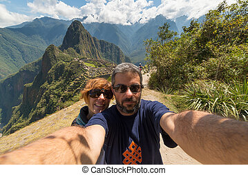 Couple taking selfie on the terraces above Machu Picchu, the most visited travel destination in Peru. Concpet of adventures in South America and people traveling aroudn the world.
