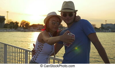 Couple taking selfie at sunset on a pontoon