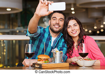 couple taking selfie by smartphone at restaurant - leisure,...