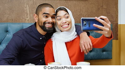 Couple taking selfie in cafeteria 4k