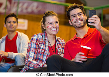 couple taking selfie in the stands during sports match