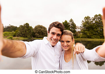 couple taking selfie together by the lake