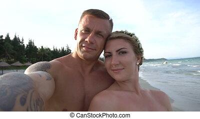Couple taking selfie using phone on beach smiling, enjoying vacation