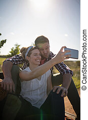 Couple taking selfie with mobile phone in a car