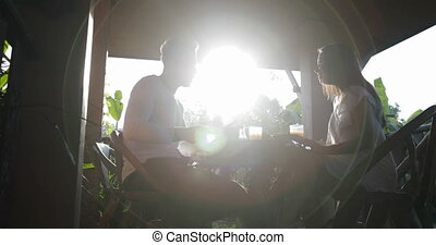 Couple Talk Eating Breakfast On Summer Terrace, Man And Woman Communication While Enjoying Healthy Meal Outdoors In Morning