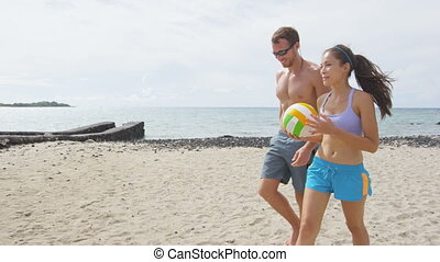 Couple talking after beach volleyball active fun living sporty active lifestyle. Portrait of people walking with volley ball after game in summer. Woman and man fitness model doing sport on beach.