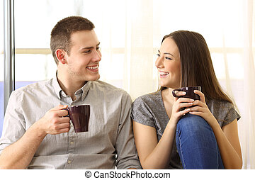 Couple talking and drinking at home