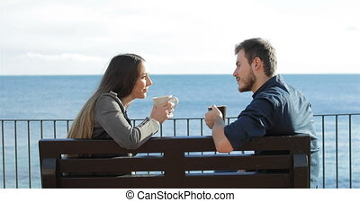 Couple talking and drinking on the beach