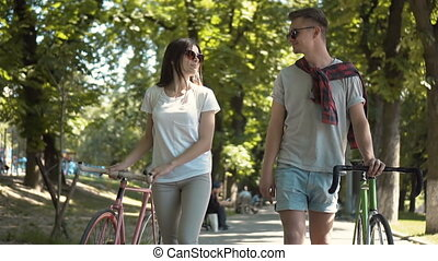 Couple Talking as Walking with Bikes