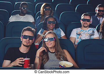 Couple talking in cinema and watching film.
