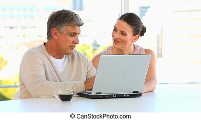 Couple talking in front a laptop