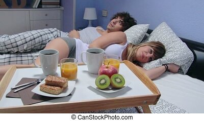Couple talking lying in bed behind of breakfast on tray -...