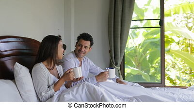 Couple Talking Sitting With Cup Of Coffee In Bed, Beautiful Girl And Man In Bedroom Morning