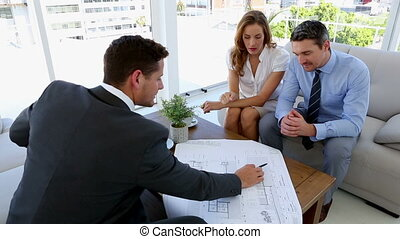 Couple talking to their architect at home on couch