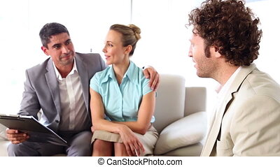 Couple talking to their financial adviser - Couple talking...