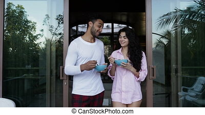 Couple Talking While Walking On Summer Terrace To Eat Breakfast, Happy Man And Woman Holding Plates With Oatmeal Outdoors