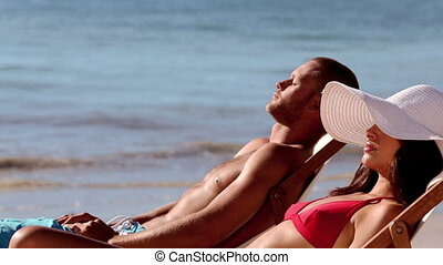 Couple tanning on the beach - Couple wearing swimsuit and...