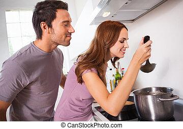 Couple tasting their dinner in kitchen