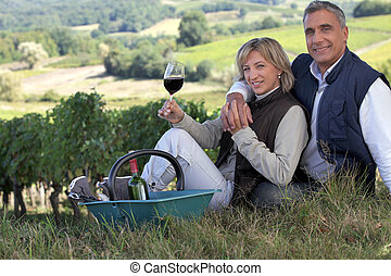 Couple tasting wine in a vineyard