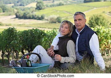 Couple tasting wine in field