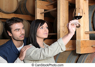 Couple tasting wine in wine cellar