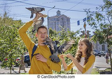 Couple teenagers feeding pigeons on city street