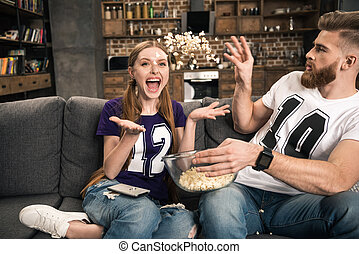 couple throwing popcorn while watching movie at home