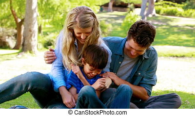 Couple tickling their son