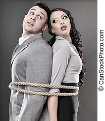Couple tied with a rope - Studio shot of young couple back ...