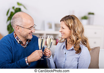 Couple Toasting Champagne Flutes While Looking At Each Other
