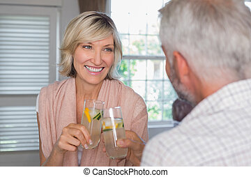 Couple toasting drinks at home