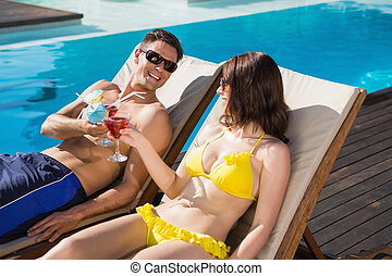 Couple toasting drinks by swimming