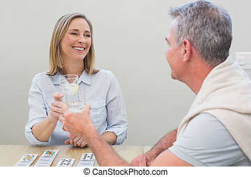Couple toasting drinks while playing cards