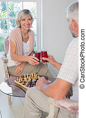 Couple toasting drinks while playing chess at home