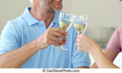 Couple toasting each other at home with glasses of white...