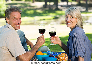 Couple toasting wine glasses in park